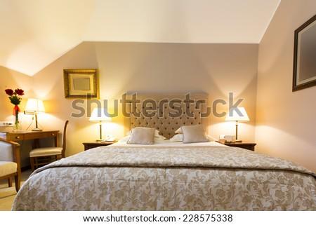 Cozy bedroom interior in the evening - stock photo