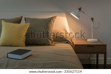 Cozy bedroom interior with book and reading lamp on bedside table - stock photo