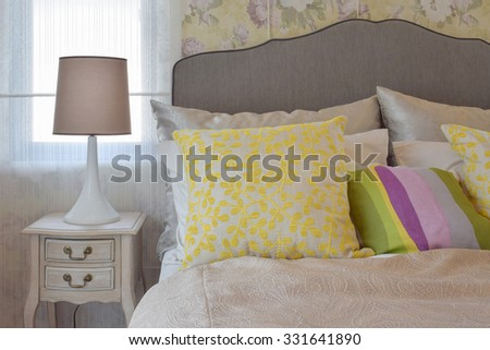 cozy bedroom interior with colorful pillow and bedside table lamp - stock photo