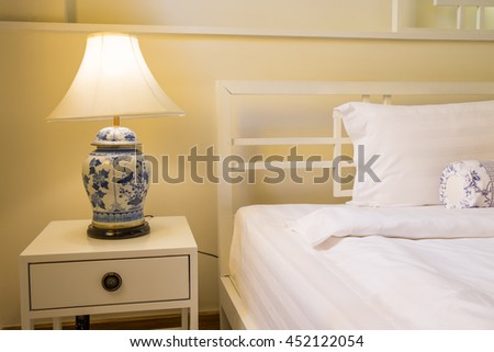 Cozy bedroom interior with pillows and retro lamp on bedside table and warm light - stock photo