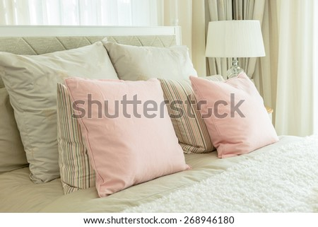 cozy bedroom interior with pink pillows and reading lamp on bedside table - stock photo