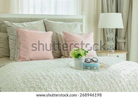 cozy bedroom interior with pink pillows and white tray of flower on bed - stock photo