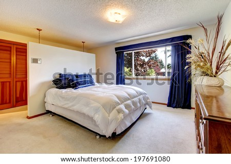 Cozy bedroom with comfortable bed and antique dresser decorated with dry branches - stock photo