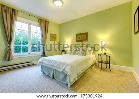 Cozy bedroom with mint wall and beige floor. Refreshing white and aqua bedding - stock photo