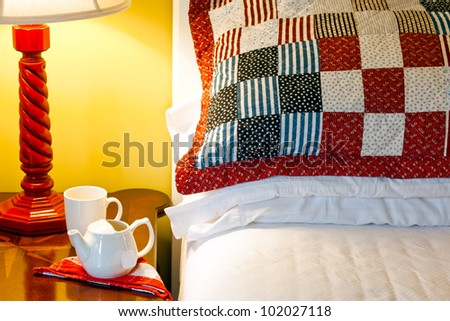 Cozy bedroom with tea on the nightstand. Closeup of pillows, lamp and vintage table. Red white and blue quilting. - stock photo