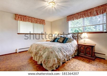 Cozy bedroom with white walls and hardwood floor. Furnished with comfortable bed, antique wooden nightstand