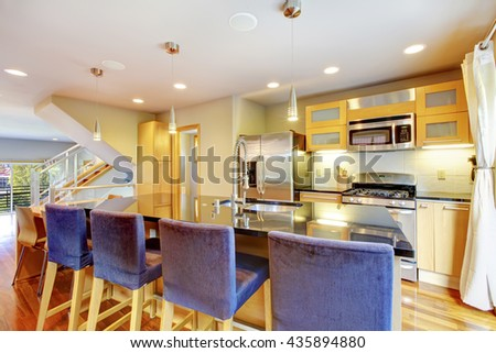 Cozy bright kitchen with    granite counter top, kitchen island, blue wooden stools and steel appliances