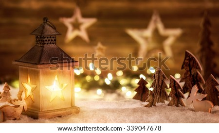 Cozy Christmas arrangement with beautiful wooden ornaments on snow in the warm candlelight of a nice lantern, low-key studio shot - stock photo
