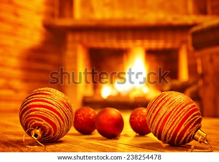 Cozy Christmas eve at home, beautiful red glass balls on the floor on fireplace background, luxury Christmas tree decoration - stock photo