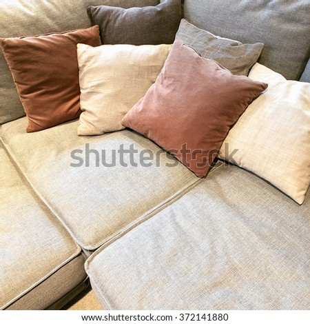 Cozy corner sofa with lots of cushions. Comfortable furniture. - stock photo