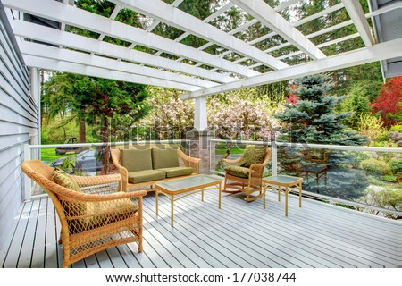 Cozy covered walkout deck with wicker and rocking chairs, settee, coffee table. Screened deck overlooking beautiful flourishing garden - stock photo