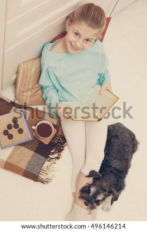Cozy home atmosphere. Little  girl reading a book near her is her dog.