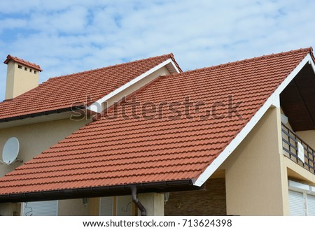 Cozy house with balcony, clay tiled roof and gable and valley type of roof construction. Building attic house construction with different types of roof designs