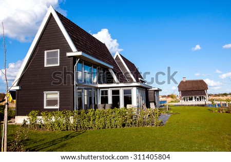 Cozy house with beautiful landscaping on a sunny day. - stock photo