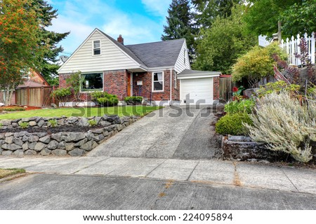 Cozy house with brick trim and front yard landscape - stock photo