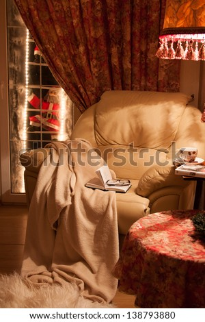 Cozy interior of the house.  A comfortable chair with a blanket, a book and a coffee. - stock photo