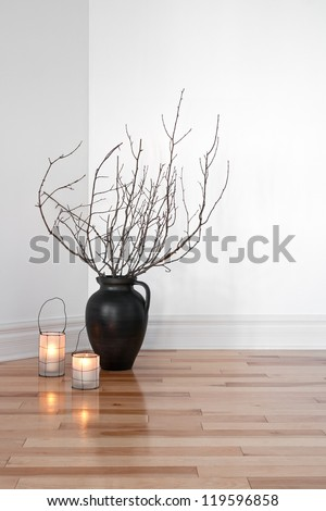 Cozy lanterns and tree branches in a vase, decorating a room. - stock photo