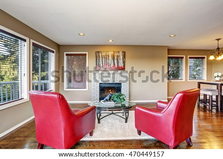 Cozy living room interior with fireplace and two red armchairs. Northwest, USA