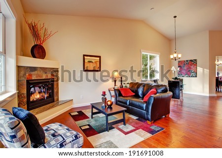 Cozy living room interior with fireplace, black leather couch and dining area - stock photo