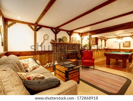 Cozy living room with ceiling beams, rustic couch, rug, wooden paneled walls, stoned background fireplace and pool table - stock photo