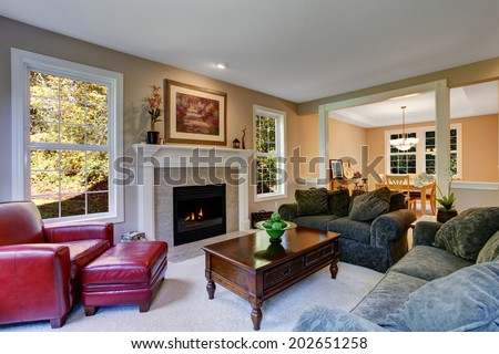 Cozy living room with fireplace, dark green sofas and red leather armchair. View of antique coffee table with drawers - stock photo