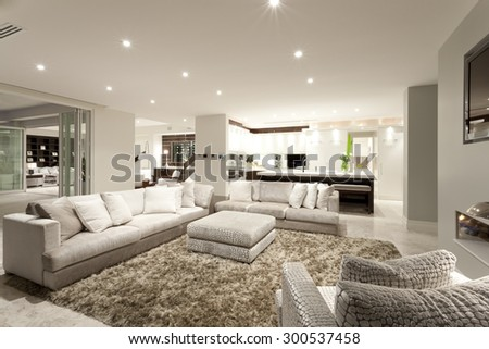 Cozy living room with two spacious sofas, an armchair and a fluffy carpet - stock photo
