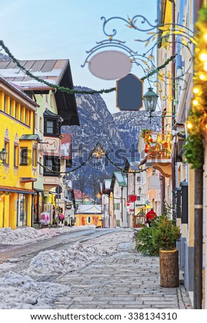 Cozy narrow street with Christmas illumination in Bavarian town of Garmisch-Partenkirchen, Germany. Seletive focus. - stock photo