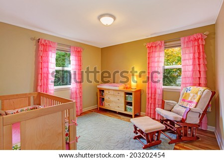 Cozy nursery room with bright pink ruffle curtains. Furnished with dresser, comfortable armchair and crib - stock photo