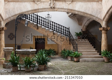 Cozy old european patio with well and stairs - stock photo
