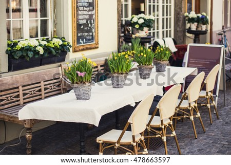 Cozy outdoor cafe in Europe with white tablecloth and flower baskets