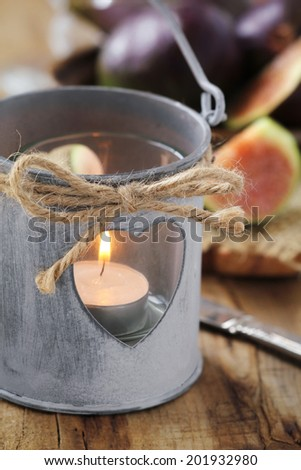 Cozy outdoor dinner - Romantic shabby chic style lantern with a lit tealight candle and fresh figs at the background - stock photo