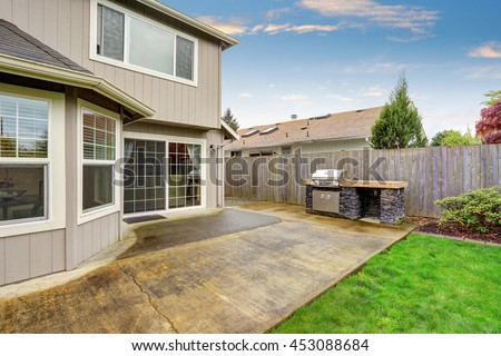 Cozy patio area with concrete floor and barbecue. Fenced spacious backyard garden with green lawn.