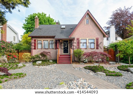 Cozy pink house with a beautiful garden on a sunny day. Home exterior.