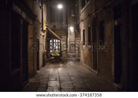 Cozy restaurant at night. Lonely dark alley with illuminated windows of a little cafe in Venice, Italy.