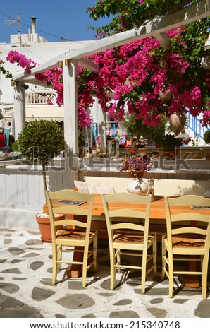 Cozy restaurant under flowering trees  in the street of Chora of Mykonos, Cyclades Island. Greece.