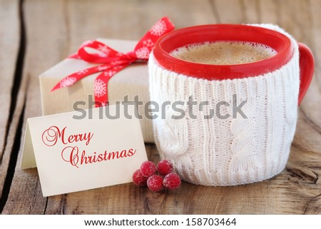 Cozy rustic Christmas setting - red mug of black coffee  in a white knitted cup holder with a wrapped gift and a greeting card - stock photo