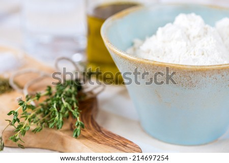 Cozy rustic home kitchen still life, dried herbs thyme, salt in white mortar - stock photo