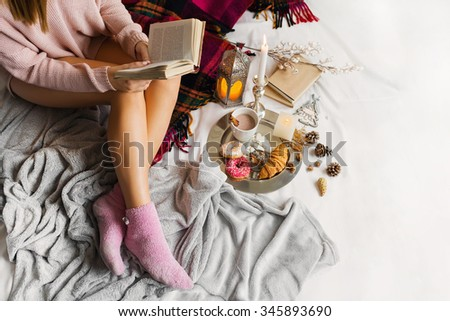 Cozy soft  image of  young woman  in warm woolen clothes is sitting on her bed  in  bright  sunny house . Girl reading book, drink coffee, stink on plaid.Burning candles,cones, christmas mood. - stock photo