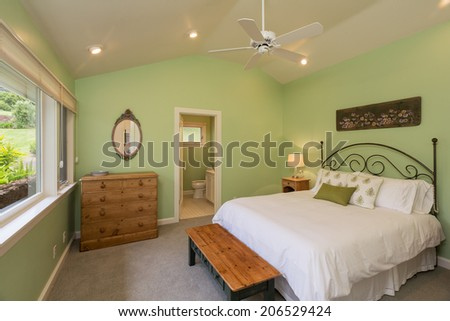 Cozy spacious bedroom in beautiful home with wood floors - stock photo