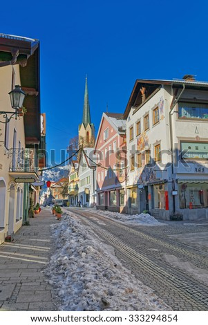 Cozy street with lovingly painted houses and Maria-Himmelfahrt (Assumption day) church in Garmisch-Partenkirchen. It is a mountain resort town in Bavaria, southern Germany, in the heart of the Alps - stock photo