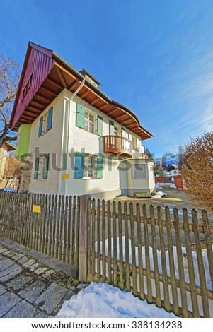 Cozy summer house in Garmisch-Partenkirchen with bright green shutters and a brown wooden roof. Selective focus. - stock photo