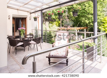 Cozy verandah with garden furniture and deckchair