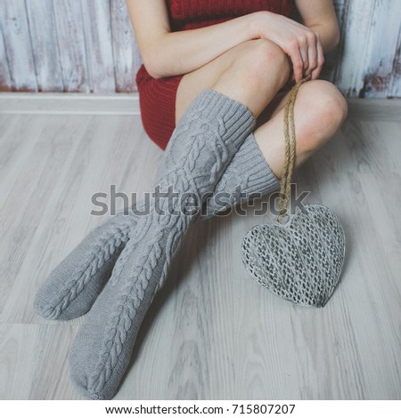 Cozy winter evening , warm woolen socks. Woman relaxing at home. Comfy lifestyle.
