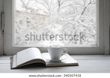 Cozy winter still life: cup of hot coffee and opened book on vintage windowsill against snow landscape from outside. - stock photo