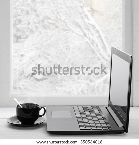 Cozy winter still life: laptop and cup of hot coffee on windowsill against snow landscape from outside. - stock photo