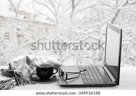 Cozy winter still life: laptop, glasses, cup of hot coffee and warm plaid on windowsill against snow landscape from outside. - stock photo