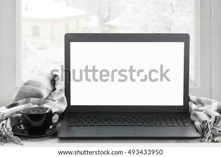Cozy winter still life: laptop with blank screen, cup of hot coffee and warm plaid on windowsill against snow landscape from outside.