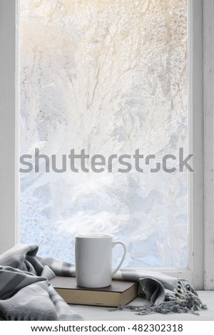Cozy winter still life: mug of hot tea and book with warm plaid on windowsill against frost pattern on window.