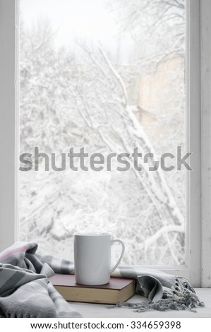 Cozy winter still life: mug of hot tea and book with warm plaid on windowsill against snow landscape from outside. - stock photo