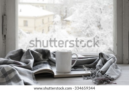 Cozy winter still life: mug of hot tea and opened book with warm plaid on vintage windowsill against snow landscape from outside. - stock photo